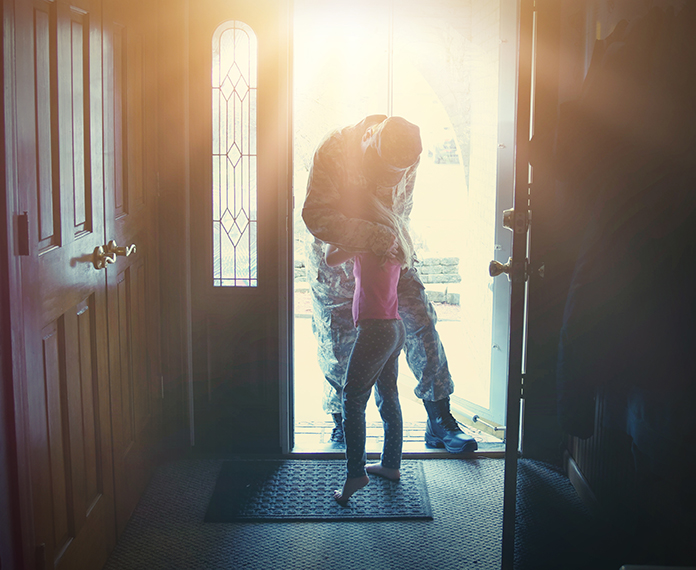 Military dad returns home and embraces daughter in doorway