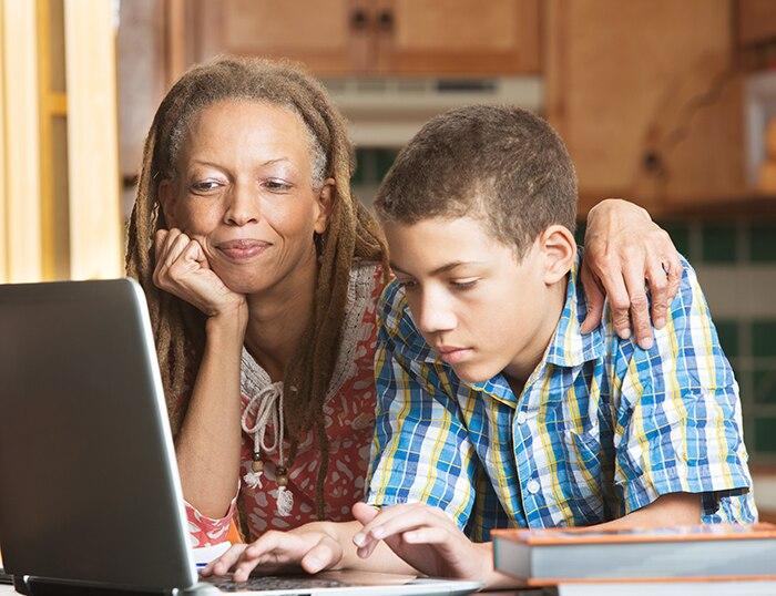 Una niña y su madre miran un computadora portátil