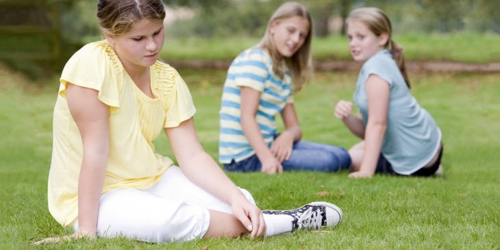 Girls bullying another girl outdoors