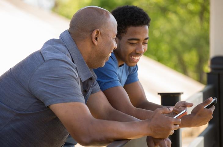 Un hombre y un adolescente hablan con sus teléfonos en la mano