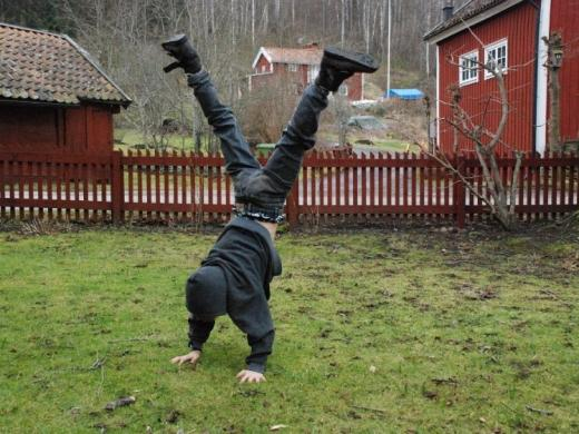 Boy doing cartwheel in yard