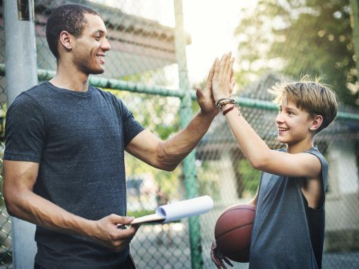 A young boy carrying a basketball is high-fiving an adult male carrying a clipboard on an outdoor basketball court.