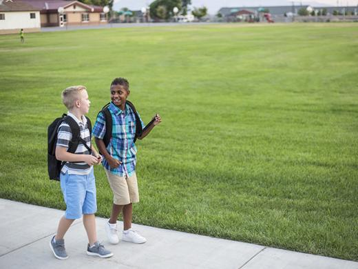 Two diverse school kids walking home together after school and talking together. Back to school photo of  diverse school children wearing backpacks in the school yard