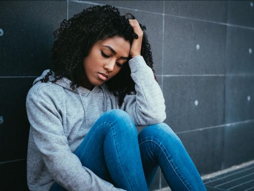A teen girl looks sad as she sits on the ground against a wall and rests her head in her hand.
