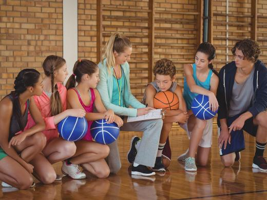 A basketball coach kneels on the court as she talks with her youth team during practice.